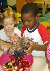 Day Nursery preschoolers add blueberries to the bowl for fruit pizza