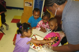 Day Nursery preschoolers spread the fruit over the cookie and creme cheese crust of their fruit pizza.